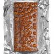 Chocolate bar with hazelnuts in aluminum foil — Stock Photo