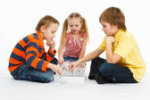 Two boys and pretty girl playing chess — Stock Photo