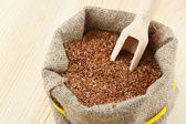 Linseed, flax seeds with wooden scoop in sack on wooden t — Stock Photo