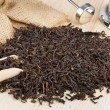 Black tea pile, wooden scoop, teapot - Foto Stock