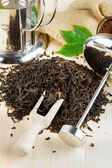 Black tea pile, teapot, wooden scoop — Stock Photo
