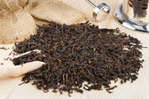 Black tea pile, wooden scoop, teapot — Stock Photo