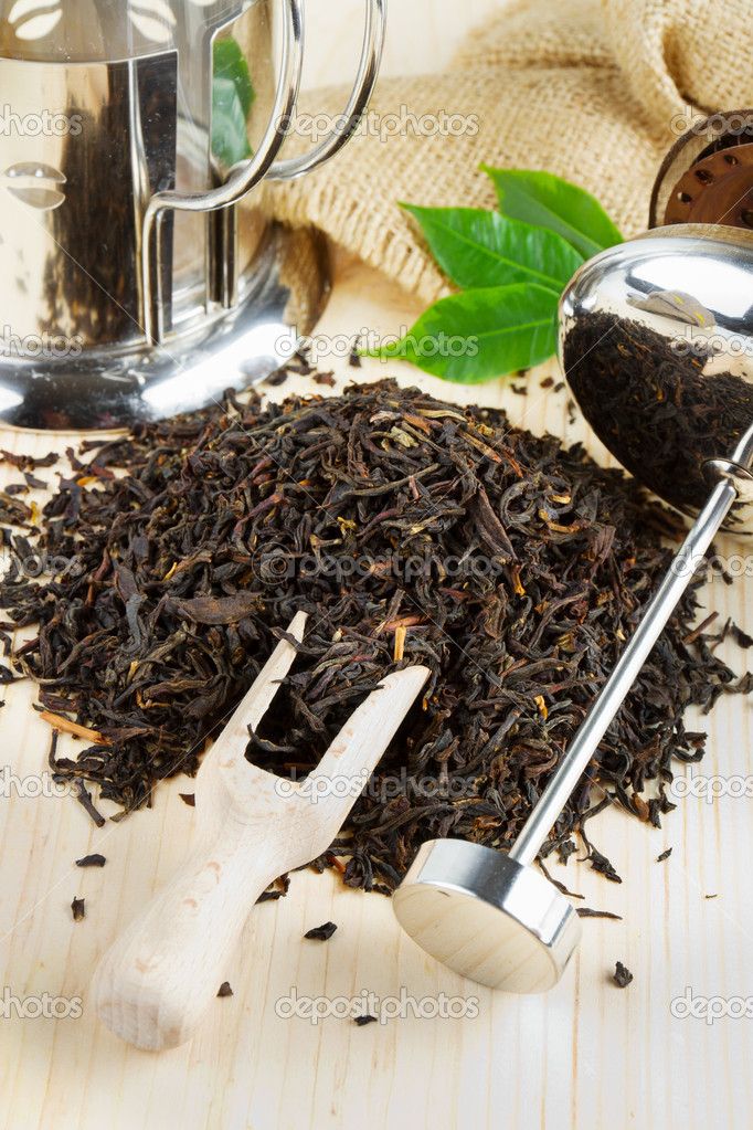 Black tea pile, teapot, wooden scoop on table — Stock Photo #9912369