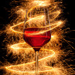 Wine in glass with burning sparklers on black background — Stock Photo