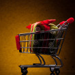 Shopping cart with gift on yellow background — Stock Photo #8407695