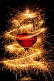 Wein im glas mit brennenden wunderkerzen auf schwarzem hintergrund — Stockfoto