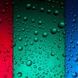 Water drops on red, green and blue backgrounds — Stock Photo