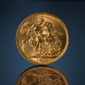 Old golden sovereign coin on blue — Stock Photo