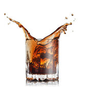 Splash of cola in glass with ice cubes isolated on white — Stock Photo