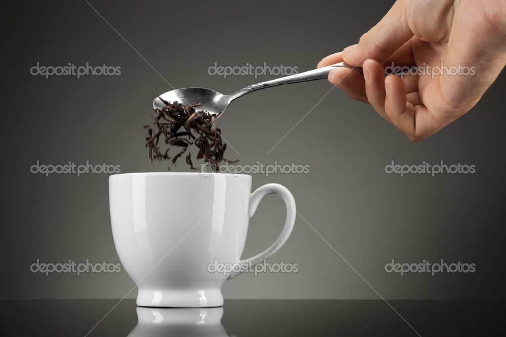 Tea pour out into white cup on grey — Stock Photo #9539615