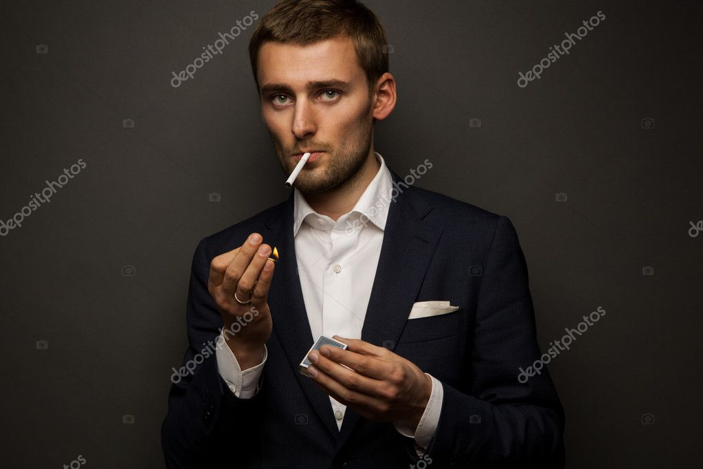 Portrait of handsome businessman with cigarette on black — Stock Photo #9824007