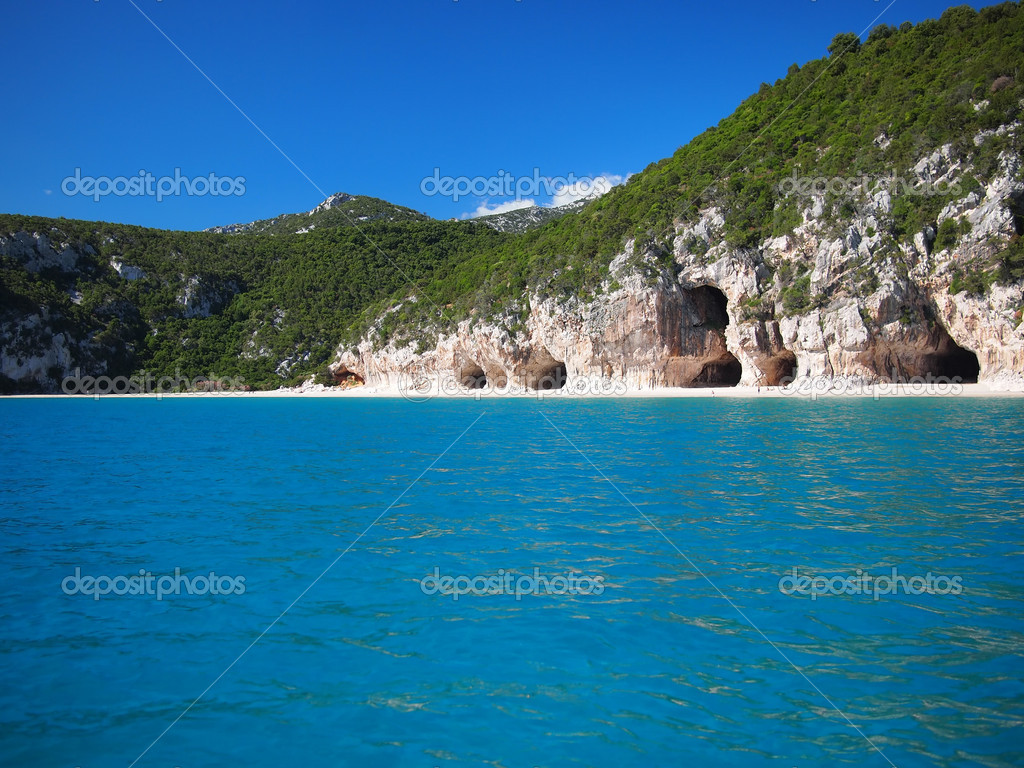 Blue sea and the characteristic caves of Cala Luna, a beach in the Golfo di Orosei, Sardinia, Italy. — Stock Photo #8830201
