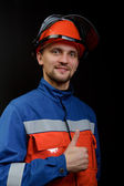 The worker in overalls and a helmet — Stock Photo