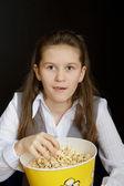 Chica sorprendida con palomitas de maíz en un fondo negro — Foto de Stock