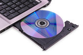 Laptop on white background. DVD disc in the drive. — Stockfoto