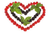 Heart made out of raspberries and blackberries. Top leaves of bl — Stock Photo
