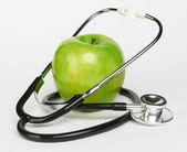 Apple and stethoscope — Stock Photo
