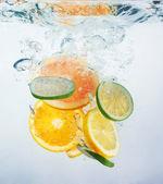Fresh orange dropped into water — Stock Photo