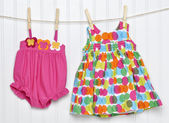 Baby Dress and Bathing Suit on a Clothesline — Stock Photo