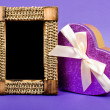 Wooden photo frame and heart gift box with ribbon on blue backgr - Stockfoto