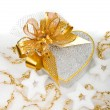 Christmas silver heart gift box with golden ribbon in snow on a — Stok fotoğraf