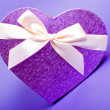Stock Photo: Single heart gift box with ribbon on blue background.