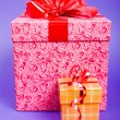 Orange and pink gift box with red ribbon on blue background. — Stock Photo