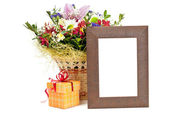 Gift box and wooden picture frame with flowers on white backgrou — Stock Photo