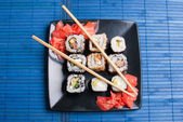 Sushi on a black plate on table. — Stockfoto