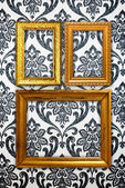 Gold frame on vintage wallpaper background — Foto de Stock