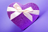 Single heart gift box with ribbon on blue background. — Стоковое фото
