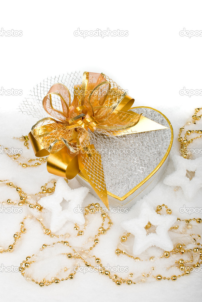 Christmas silver heart gift box with golden ribbon in snow on a white background. — Foto Stock #10122105