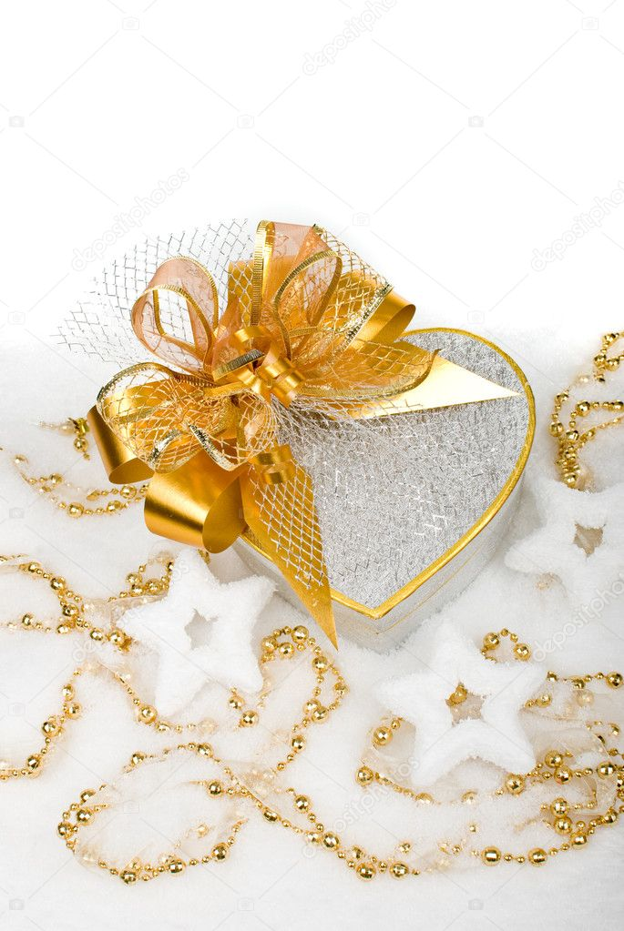 Christmas silver heart gift box with golden ribbon in snow on a white background. — Photo #10122105