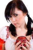 Donna attraente tenendo palla di natale rossa su sfondo bianco — Foto Stock