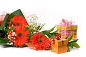 Beautiful bouquet of gerber and present boxes on a white — Stock Photo