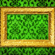 Royalty-Free Stock Photo: Gold frame on a vintage green wall background