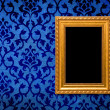 Gold frame on a vintage blue wall background — Stock Photo #8070690