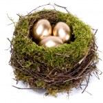 Beyaz arka plan üzerinde izole yuvaya üç altın yumurta — Stok fotoğraf