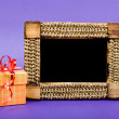 Wooden photo frame and orange gift box with red ribbon on blue b — Stockfoto