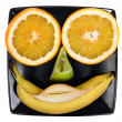 Royalty-Free Stock Photo: Smiling face made of orange, banana and apple on the black plate