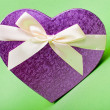Single heart gift box with ribbon on green background. — Foto de Stock