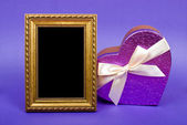 Gold photo frame and heart gift box with ribbon on blue backgrou — Stock Photo