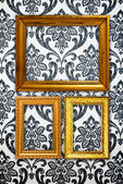 Gold frame on vintage wallpaper background — Stock Photo
