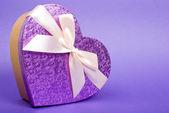 Einzelnen herz-geschenk-box mit band auf blauem hintergrund. — Stockfoto