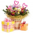 Beautiful bouquet in the basket and present boxes on a white bac — Stock Photo