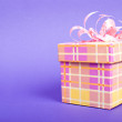 Single yellow gift box with pink ribbon on blue background. — Stock Photo