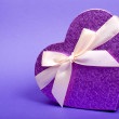 Single heart gift box with ribbon on blue background. — Foto Stock