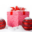 Christmas gift box in the snow with red balls and candles — Stock Photo #9727812