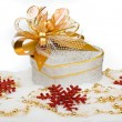 Stockfoto: Christmas silver heart gift box with golden ribbon in snow on a