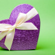 Single heart gift box with ribbon on green background. — Stok fotoğraf